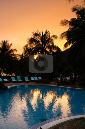 Sunset swimingpool stock photo, Sunset at a swimmingpool with silhouette palm trees by Karin Claus