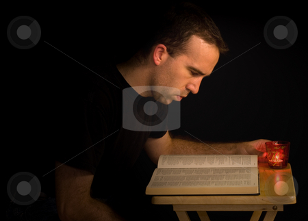 Reading At Night stock photo, A young man reading a book with candle light by Richard Nelson