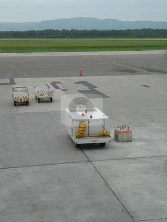 Empty airplane gate with small trucks stock photo,  by Mbudley Mbudley
