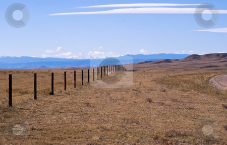 Cattle fence on the high plains stock photo, Rocky Mountains in the background of a high plains drift fence. by RCarner Photography