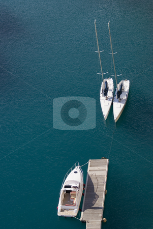 Boats stock photo, Aerial view of two sailboats and one motorboat in a deep blue lagoon. Mediterranean sea - French Riviera. by Serge VILLA