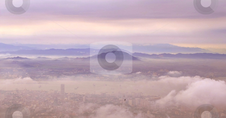Dreaming clouds stock photo, Clouds above a city and mountains seen from above by Karin Claus