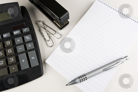 Office Scene stock photo, A desktop calculator, stapler and paper clips stands next to a blank writing pad with a stylish pen atop by Steve Smith