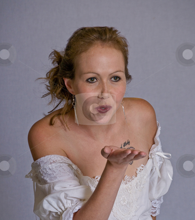 Young woman blowing a kiss stock photo, Sexy young woman with bare shoulders blows a kiss by RCarner Photography