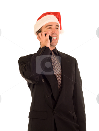Christmas Phone Call stock photo, A young businessman on the phone while wearing a santa cap by Richard Nelson