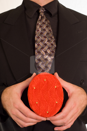 Christmas Gift stock photo, A christmas gift being held in front of a business suit by Richard Nelson