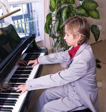 Young man preparing for recital stock photo, A young boy practices his piece for a recital by RCarner Photography