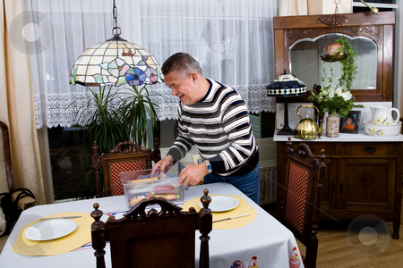 Grandfather is setting the table for breakfast stock photo, Older man is preparing breakfast by Frenk and Danielle Kaufmann