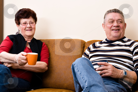 Senior couple drinking cofee and talking stock photo, Cousy scene of a elderly couple sitting and relaxing by Frenk and Danielle Kaufmann