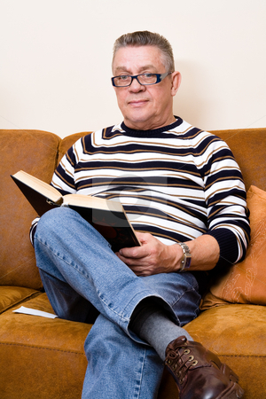 Senior reading his book on the couch stock photo, Older man reading a book sitting on his couch by Frenk and Danielle Kaufmann