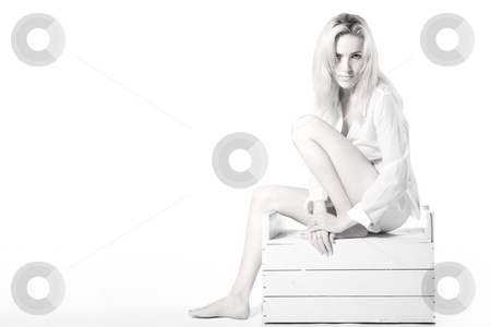 Woman sitting on a wooden case stock photo, Portrait of a sexy woman sitting on a white case by Frenk and Danielle Kaufmann