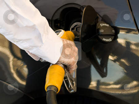 Fill up tank stock photo, Man wearing protective gloves filling up  his car tank with a yellow nozzle by Laurent Dambies