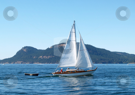 Sailboat on Bay with dingy trailing behind stock photo, Sailboat with dingy on Bay  blue sky and water by Jeff Cleveland