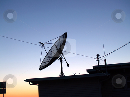 Satelite Dish silhouette on house blue sky stock photo, Satelite Dish on top of dwelling blue sky by Jeff Cleveland