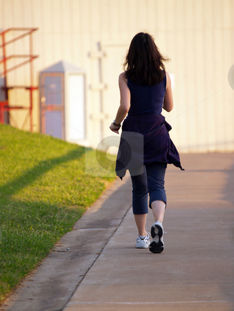 Woman Walking for Exercise next green grass  stock photo, Young woman walking for exercise next green grass by Jeff Cleveland