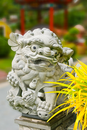 Asian religious lion   stock photo, Grey stone religious asian lion with a out of focus background by Karin Claus