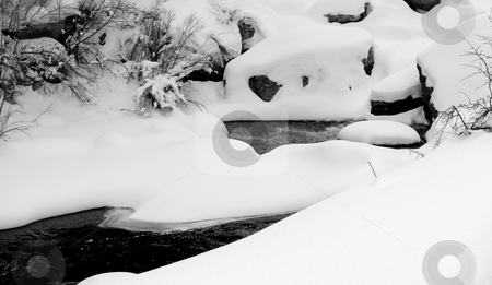 Snow Drifts on a Mountain River stock photo, Snow drifts create unusual shapes over the boulders of a mountain river in Colorado. by John McLaird