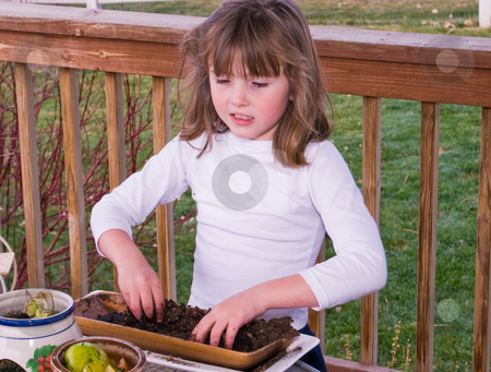 Got to mix it up good stock photo, Little girl playing with gardening dirt by RCarner Photography