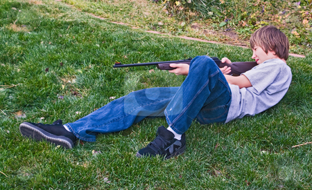 Teenage boy practicing with a bb gun stock photo, Teenager practices shooting with a pellet gun by RCarner Photography