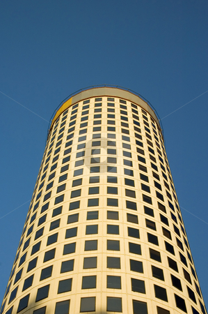 Round Office Tower on Blue Sky stock photo, A tall and round form office building with more than 20 levels pictured from below on a blue sky. by Lee Torrens