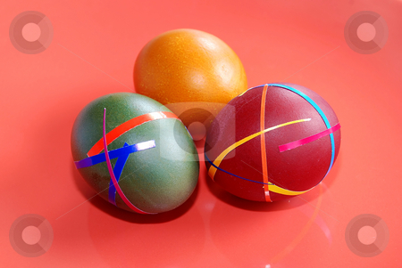 Easter eggs stock photo, Three colored ester eggs isolated over red by Julija Sapic