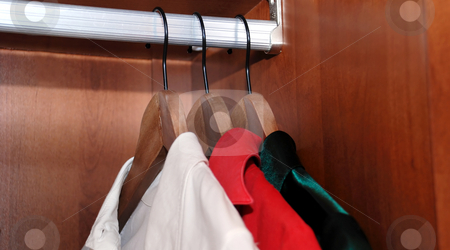 Wardrobe stock photo, Three clothes-hanger with chemises in wooden wardrobe by Julija Sapic