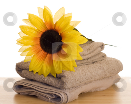 Relaxation Time stock photo, An artificial sunflower resting on some towels by Richard Nelson