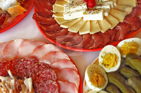 Appetizing meat dishes stock photo, Meat and cheese slices served on plates by Julija Sapic