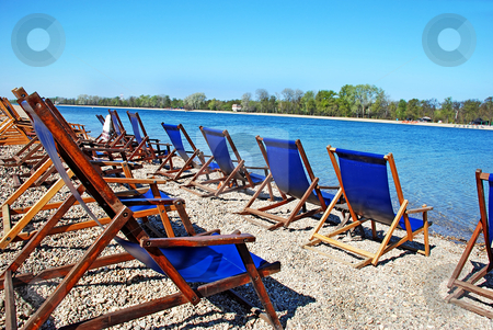 Blue folding chairs stock photo, Row of  folding chairs by on beach by blue water by Julija Sapic