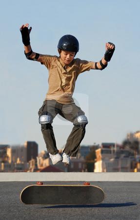 Boy Jumping from Skateboard stock photo, Boy jumping from skateboard wearing protective gear by Denis Radovanovic