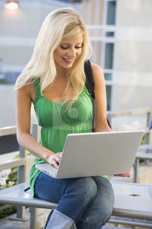 Female student using laptop outside stock photo, Female university student using laptop outside by Monkey Business Images