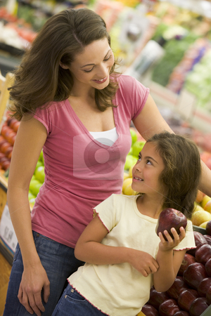 Mother and daughter shopping in produce section stock photo, Mother and daughter shopping in produce section of supermarket by Monkey Business Images
