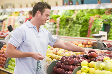 Man shopping in produce section  stock photo, Man shopping in produce setion of supermarket by Monkey Business Images
