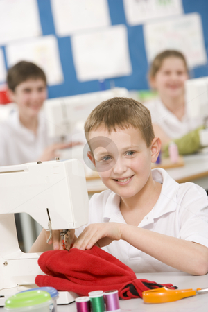 Schoolboy using a sewing machine in sewing class stock photo,  by Monkey Business Images