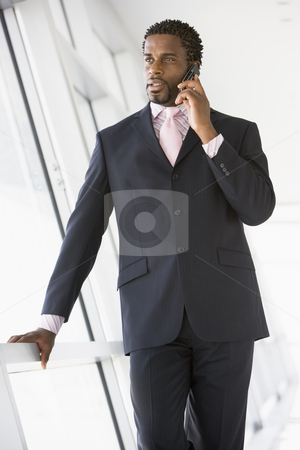 Businessman standing in corridor using cellular phone stock photo,  by Monkey Business Images