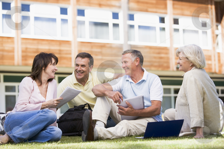 Adult students sitting on a campus lawn stock photo,  by Monkey Business Images