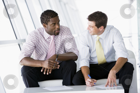 Two businessmen sitting in office lobby talking and smiling stock photo,  by Monkey Business Images