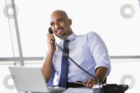 Businessman talking on phone stock photo, Businessman talking on phone in office by Monkey Business Images
