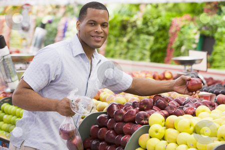 Man shopping in produce section stock photo, Man shopping in produce section of supermarket by Monkey Business Images