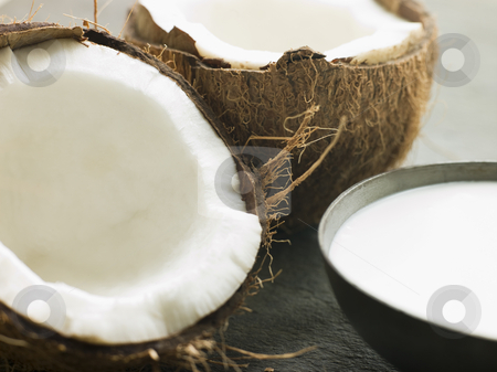 Dish of Coconut Milk with a Split Fresh Coconut stock photo, Close up of Dish of Coconut Milk with a Split Fresh Coconut by Monkey Business Images