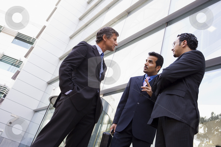 Group of businessmen talking outside office building stock photo, Group of businessmen talking outside modern office building by Monkey Business Images