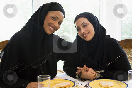 Two Middle Eastern women enjoying a meal  stock photo,  by Monkey Business Images