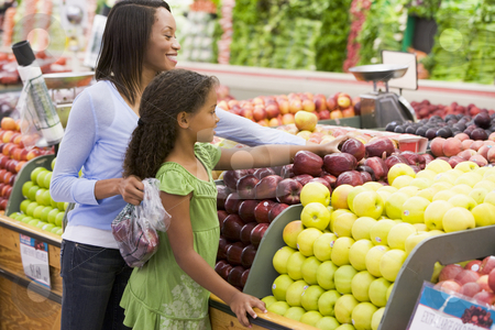 Mother and daughter in produce section stock photo, Mother and daughter in supermarket produce section by Monkey Business Images