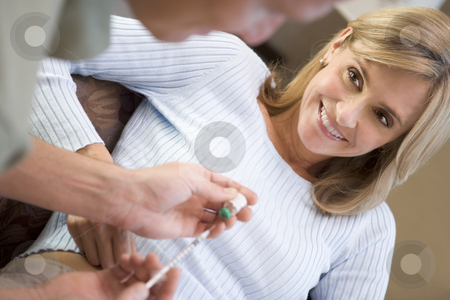 Man helping woman inject drugs to prepare for IVF treatment stock photo, Man helping woman inject drugs to prepare for IVF treatment at home by Monkey Business Images