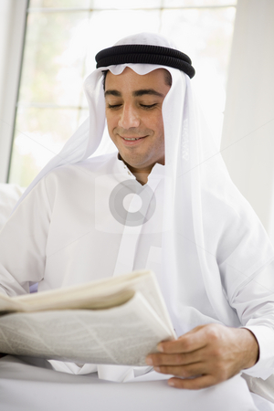 A Middle Eastern man reading a newspaper stock photo,  by Monkey Business Images