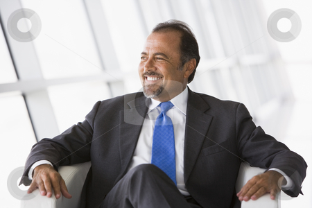 Businessman sitting in chair in lobby stock photo, Businessman sitting in chair in office lobby by Monkey Business Images