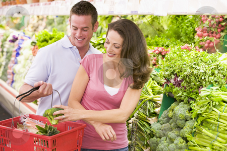 Couple shopping in produce section stock photo, Couple shopping in supermarket produce section by Monkey Business Images