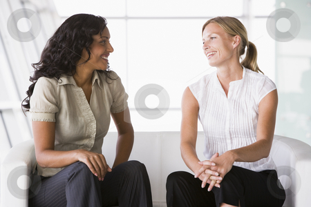 Businesswomen talking in lobby stock photo, Businesswomen talking in office lobby by Monkey Business Images