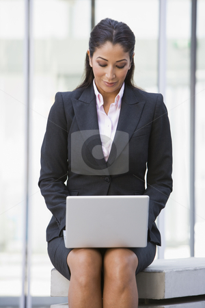 Businesswoman using laptop computer outside stock photo, Businesswoman using laptop computer outside office by Monkey Business Images