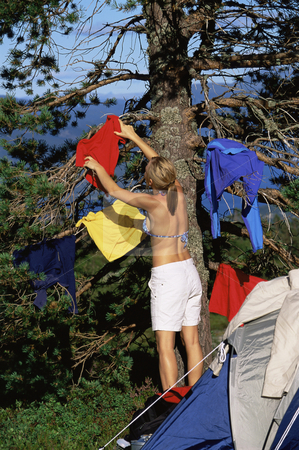 Young woman hanging out washing on a tree next to campsite stock photo,  by Monkey Business Images
